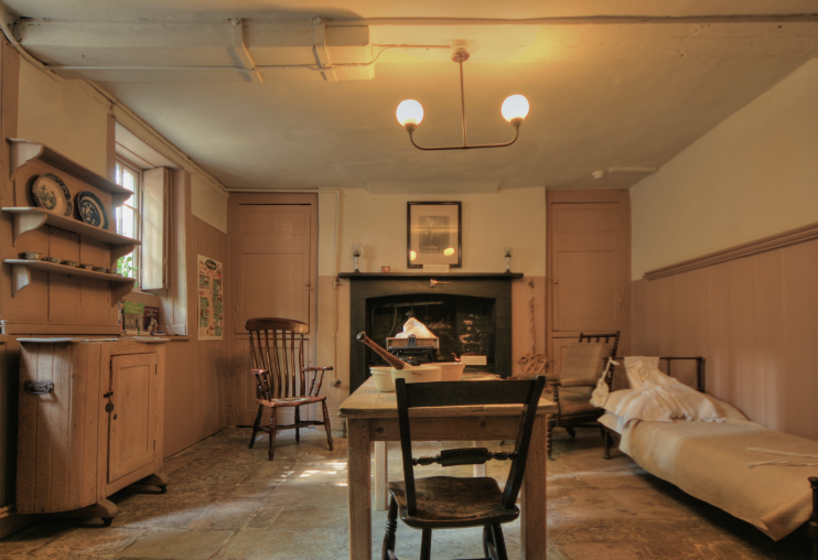 The ochre and brown kitchen at Carlyle's House, with a bed for the maid