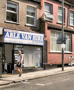 A terraced house offering car rental with a pot-bellied man in a t-shirt and shorts walking past