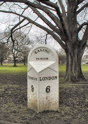 A milepost at the edge of a muddy Ealing Common, seen on a dull day