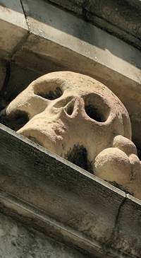 A stone skull above the entrance to St Olave's churchyard