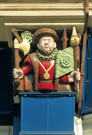 Carved relief of Henry VIII adorning the former Eagle & Child public house, adapted from an original photograph, copyright Julian Osley