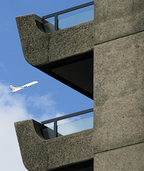 An airliner passes Cromwell Tower