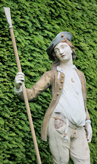 Painted statue of a young man in 18th-century costume, on the lawn facing the rear of the house